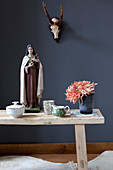Flowers and Madonna figurine on wooden bench in front of hunting trophy on dark wall