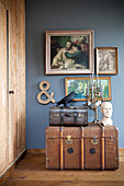 Vintage trunk, bust, candelabra and bird figurine below paintings on dark wall