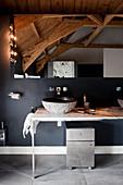 Filigraner Waschtisch und Spiegel an schwarzer Wand mit Holzdecke