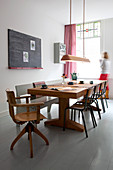 Solid wooden dining table with chairs and bench next to chalkboard on wall
