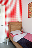 Wooden bed with tall headboard against wall covered in red-and-white gingham wallpaper