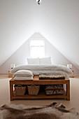 Holzbank am Bettende in weißem Schlafzimmer im Dachgeschoss
