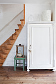 White cupboard in hallway next to wooden staircase