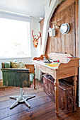 Vintage-style swivel chair made from wooden boards and bureau in room with wooden wall
