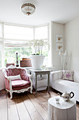 Comfortable armchair and large pot of orchids on wooden table in window bay