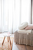 Fringed blanket and cushions on ottoman and stool in front of window with floor-length curtains