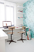 Desk with two chairs in study with turquoise floral wallpaper