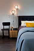 Doppelbett mit schwarzem Bettkopfteil und Wandleuchten im Schlafzimmer