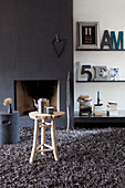 Fireplace in dark chimney breast and decorative letters on shelves in living room with grey long-pile rug