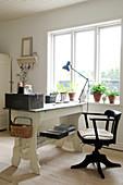 Alter Drehstuhl und Schreibtisch mit Vintage-Deko am Fenster