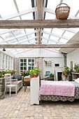 Conservatory with brick floor and glass roof as a guest house with bed
