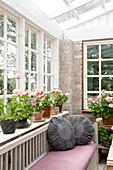 Graue runde Kissen auf der Bank vorm Sprossenfenster mit Geranien auf der Fensterbank