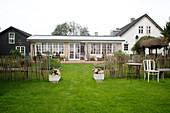 Eingang mit Pflanztrögen im Staketenzaun zum Garten und Haus