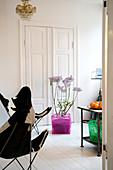Butterfly-Chair und Flieder im pinken Plastikkorb vor einer Kassettentür