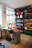 Shelf with rolls of fabric and boxes in the sewing room with a wooden plank floor