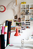 Shelf with buttons and picture gallery above a sewing table in a craft room