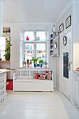 Truhenbank unterm Fenster in der Küche mit weißem Dielenboden