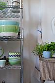 Geschirr in Grün und Blau in einem Metallregal