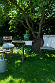 seating area with old garden furniture on the meadow in the summer garden