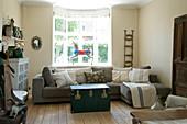 Graues Sofa und Truhe als Couchtisch im Wohnzimmer in Naturtönen