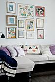 Bildergalerie überm Sofa im Wohnzimmer mit dunklem Holzboden