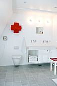 A medicine cabinet in a cross shape above the toilet in the modern bathroom