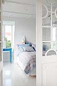 Glastür zum Schlafzimmer mit weißem Boden und blauen Farbakzenten