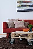 Palette auf Möbelrollen als Couchtisch vorm roten Sofa