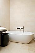 Oval freestanding bathtub in the modern bathroom in light beige