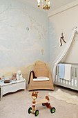 Slide vehicle in the baby room with wall painting and cot