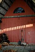 Gartenwerkzeug und Stuhl mit Fell am roten Holzhaus im Herbst