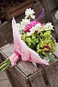 Blumenstrauß mit Pfingstrosen, Frauenmantel und Bauernjasmin mit Papiermanschette
