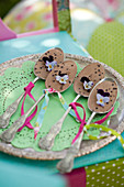 Silver spoons filled with chocolate and decorated with ribbons and violas