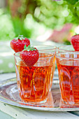 Strawberries on rims of glasses of strawberry squash