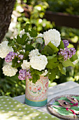 Bouquet of viburnum and lilac in vintage vase
