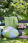 Round, pale blue and green patchwork cushion in garden