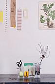 Utensilo aus transparentem Kunststoff mit Schreibtischzubehör unter einer Collage