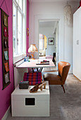Desk and retro leather armchair below window flanked by hot-pink walls