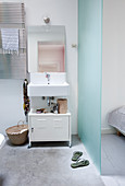 Sink above white metal cabinet in ensuite bathroom