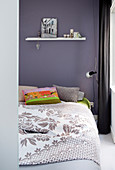 Double bed with bedspread and colourful scatter cushions against purple bedroom wall