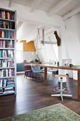 Long dining table with various chairs and bookcase in open-plan interior
