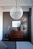 Double bed, spherical lampshade and antique chest of drawers in bedroom in shades of grey