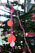 Christbaumkugeln aus Papier und bunte Perlenkette am Weihnachtsbaum