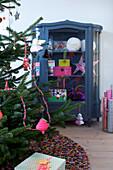 Weihnachtsbaum mit selbstgemachter Deko vorm grauen Vitrinenschrank