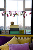 Girlande mit Weihnachtsschmuck am Fenster, Schachteln auf dem Fenstersims