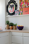 ceramic pots with kitchen herbs and colorful pictures on a picture ledge in a kitchen