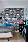 Girlande mit Bildern an einer Ornamente-Tapete im Schlafzimmer