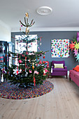 Christmas tree on round carpet in colorful living room
