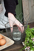 Woman placing glass of water in metal basket