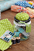 Sewing utensils in screw-top jar with pin cushion on lid